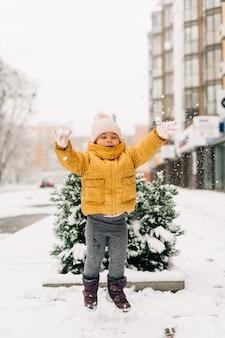 Peuterkind in gele uitloper op besneeuwde dag buiten met pijnboom bedekt met sneeuw