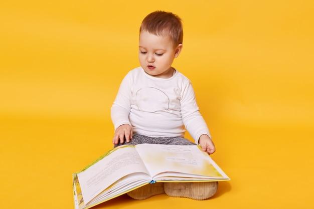 Peutermeisje doet alsof ze boek leest terwijl ze op de vloer zit, foto's bekijkt en pagina's omslaat, meisje kijkt geconcentreerd