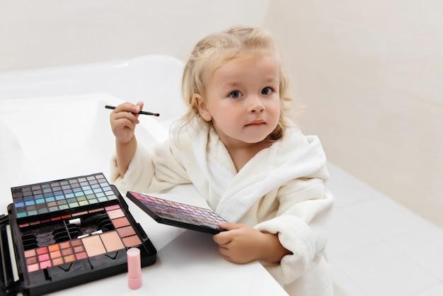 Peutermeisje doet make-up met oogschaduw in badjas