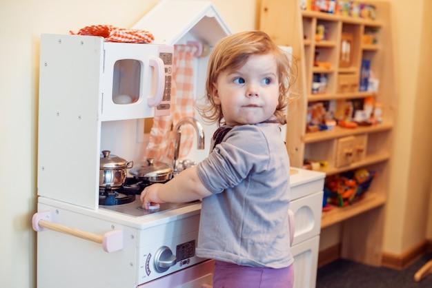 Peutermeisje het spelen stuk speelgoed keuken