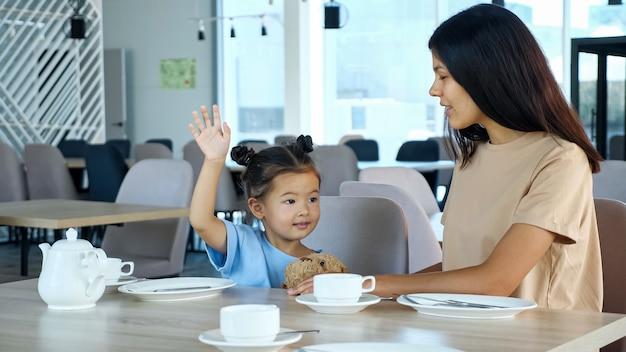 Peutermeisje steekt hand op met glimlach terwijl ze bij mama in café zit