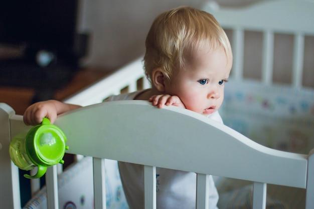 Peuters babyjongen (9-12 maanden) staat in een witte wieg en houdt een drinkfles in zijn handen
