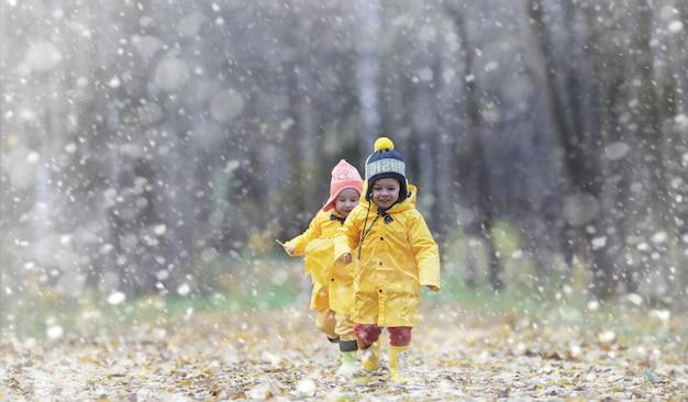 Peuters op een wandeling in het herfstpark. eerste vorst en de eerste sneeuw in het herfstbos. kinderen spelen in het park met sneeuw en bladeren.