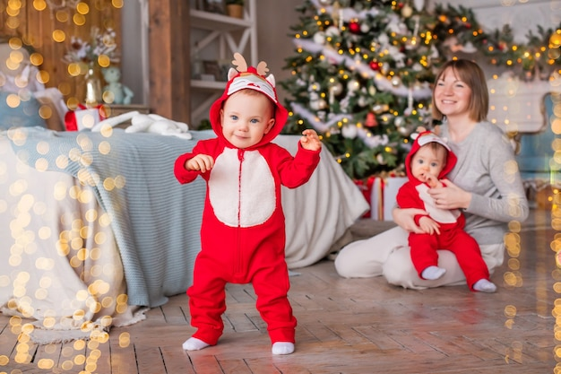 Peutertweeling in rode rendierkostuums voor kerstman zetten hun eerste stapjes thuis met hun moeder
