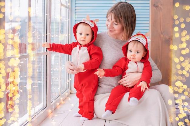 Peutertweelingen in rode rendierkostuums van de kerstman zitten thuis met hun moeder tegen de achtergrond van een raam met slingers