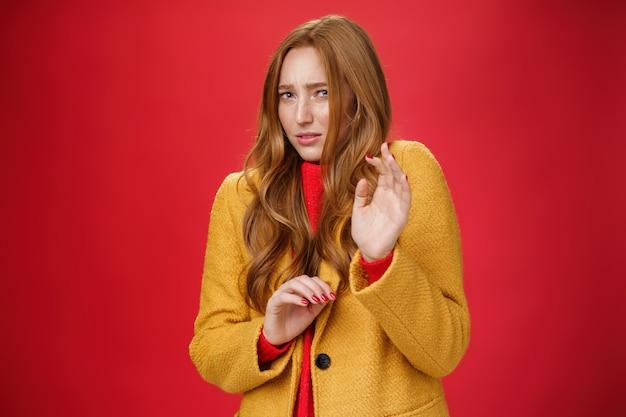Pff walgelijk haal het weg. ontevreden intense en ontevreden schattige roodharige vrouw in gele jas die handen opsteekt in de buurt van de borst ter verdediging, bukkend en grimassend van afkeer over rode achtergrond.