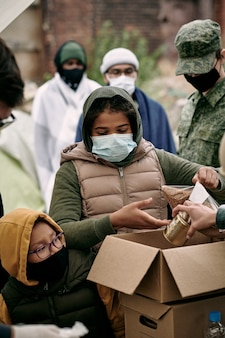 Phand van maatschappelijk werker die producten in kartonnen doos stopt aan vluchtelingenkinderen met maskers onder controle van legersoldaat