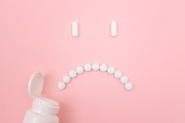 Pharma schaadt droevig smileygezicht gemaakt van witte pillen