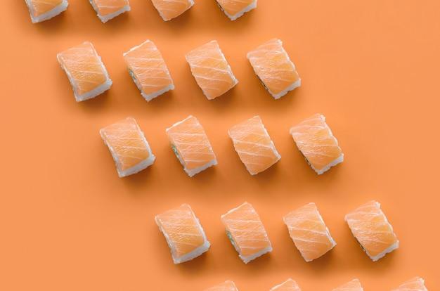 Philadelphia rolt met zalm op oranje achtergrond. minimalisme bovenaanzicht plat lag patroon met japans eten