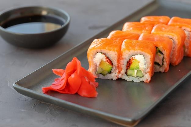 Philadelphia sushi roll geserveerd op zwarte keramische plaat close-up