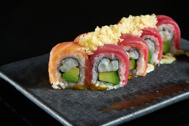 Philadelphia sushirol met zalm en tonijnkrab, avocado, geserveerd op een donker bord met wasabi en gember. isolatie op een zwarte tafel. japans eten