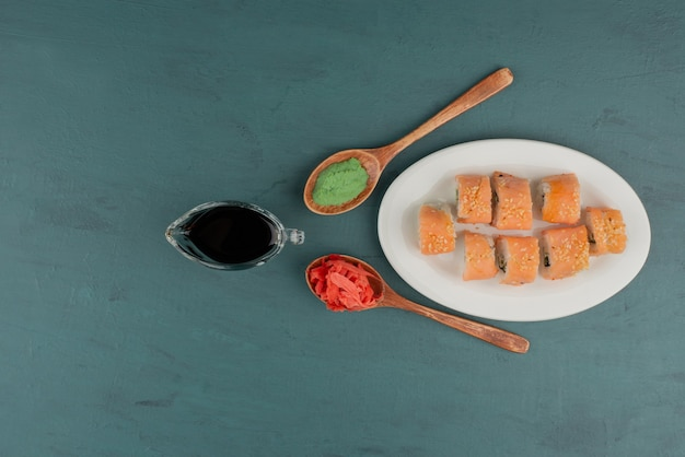 Phildelphia sushibroodje met ingelegde gember, sojasaus en wasabi op blauwe lijst.