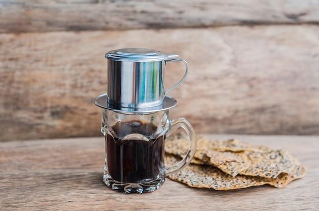'phin' traditioneel vietnamees koffiezetapparaat, plaats op het glas, voeg gemalen koffie toe, giet er heet water in en wacht tot de koffie in het glas druppelt.
