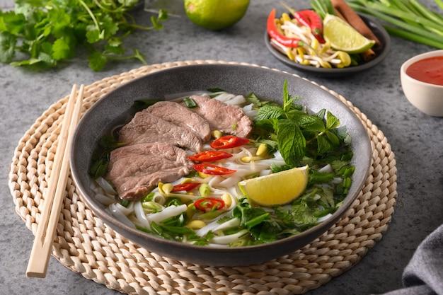 Pho bo-soep met rundvlees in grijze kom op grijze vietnamese keuken
