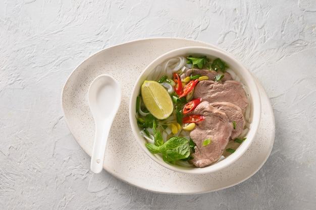 Pho bo-soep met rundvlees in kom op witte vietnamese keuken als achtergrond