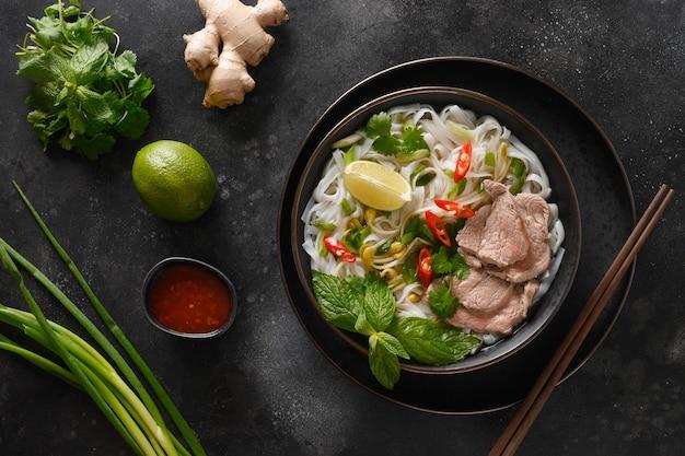 Pho bo-soep met rundvlees in kom op zwarte vietnamese keuken als achtergrond