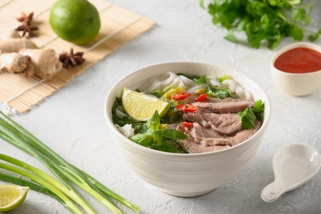 Pho bo-soep met rundvlees in witte kom op lichte vietnamese keuken als achtergrond