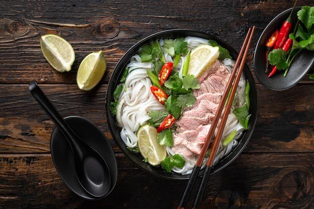 Pho bo vietnamese soep met rundvlees en noedels op een houten achtergrond, bovenaanzicht