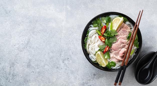 Pho bo vietnamese soep met rundvlees en rijstnoedels op concrete achtergrond, hoogste mening, exemplaarruimte