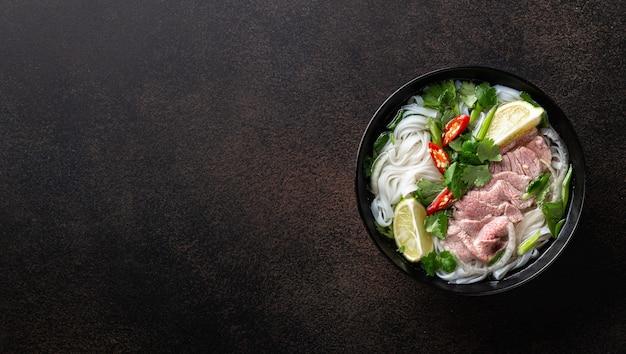 Pho bo vietnamese soep met rundvlees en rijstnoedels op een donkere achtergrond, bovenaanzicht, kopie ruimte