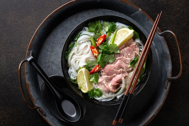 Pho bo vietnamese soep met rundvlees en rijstnoedels op een donkere achtergrond, bovenaanzicht