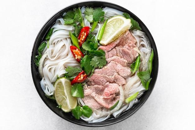 Pho bo vietnamese soep met rundvlees en rijstnoedels op een witte achtergrond, bovenaanzicht, close-up