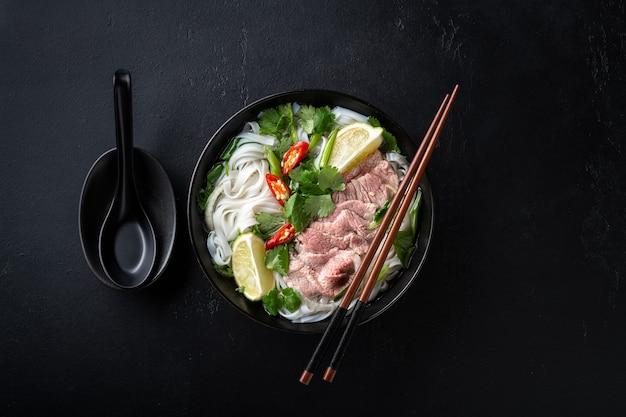 Pho bo vietnamese soep met rundvlees en rijstnoedels op een zwarte achtergrond, bovenaanzicht