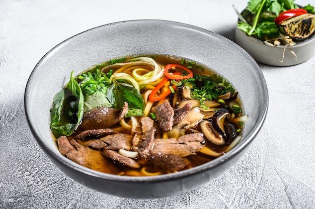 Pho bo vietnamese soep met rundvlees. witte achtergrond. bovenaanzicht