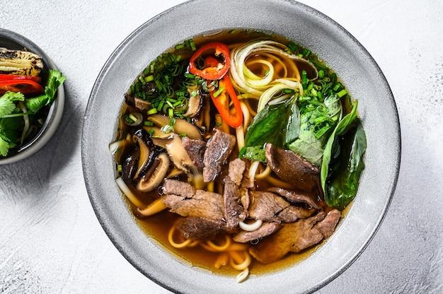 Pho bo vietnamese verse rijstnoedelsoep met rundvlees, kruiden en chili. witte achtergrond. bovenaanzicht