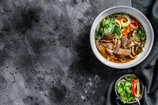 Pho bo vietnamese verse rijstnoedelsoep met rundvlees, kruiden en chili. zwarte achtergrond. bovenaanzicht. kopieer ruimte