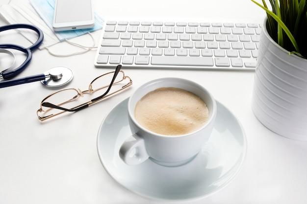 Phonendoscope, computer en koffie op een witte tafel van een arts