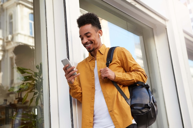 Phortrait van jonge vrolijke afro-amerikaanse man in geel shirt, op straat loopt en telefoon vasthoudt, chatten met vrienden, ziet er gelukkig en breed lachend uit.
