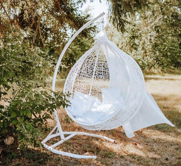 Photozone luifel hangstoel in het bos in de natuur. de stof wappert in de wind. plaats voor een foto van de bruid. fotosessie