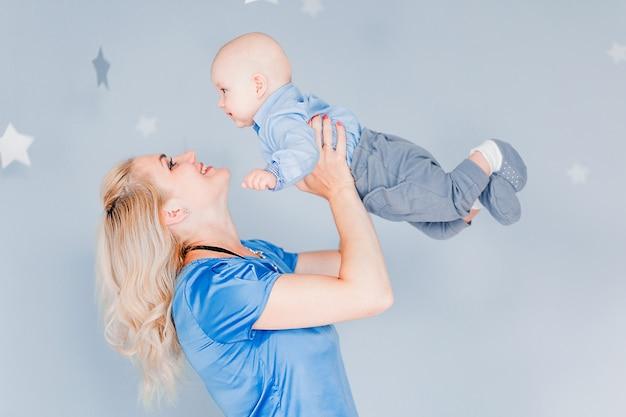 Phto van moeder speelt en werpt een kind in de kinderkamer tegen de achtergrond van de blauwe muur