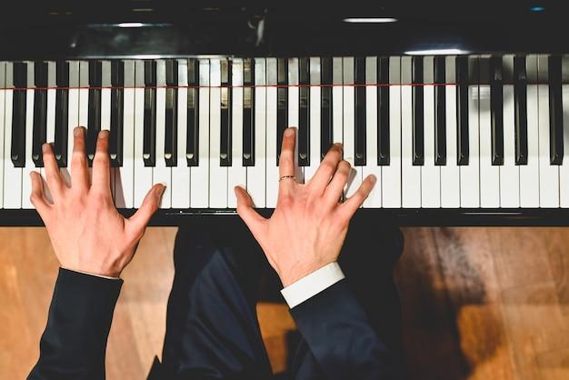Pianist die een stuk op een grote piano met witte en zwarte sleutels uitvoert.