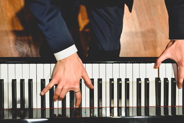 Pianist die een stuk op een grote piano met witte en zwarte sleutels uitvoert