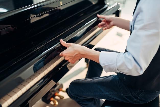 Pianist opent het klavierdeksel van de vleugel