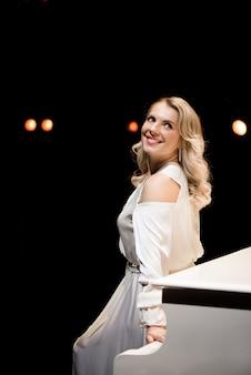 Pianist poseren in de buurt van witte piano op het podium