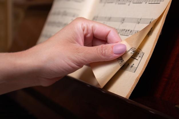 Pianisten hand draait bladmuziek pagina close-up