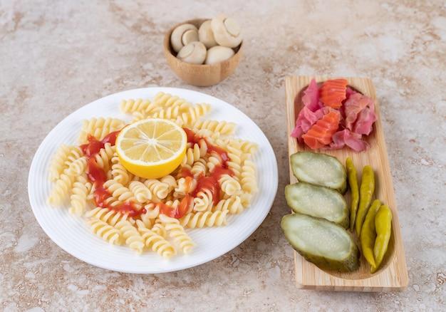 Pickle tray en champignonkom vergezeld van pastaschotel op marmeren oppervlak