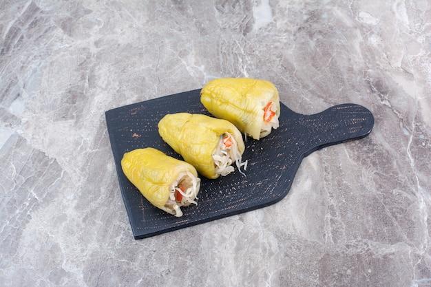 Pickles gevuld in paprika's op een donker bord.