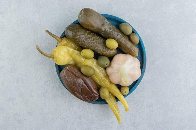 Pickles hete pepers, olijven, komkommer en aubergine op de houten plaat op het marmeren oppervlak