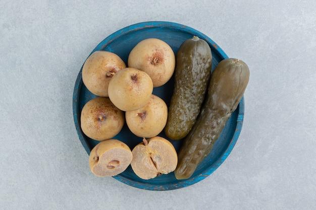 Pickles komkommer en appels op houten plaat op het marmeren oppervlak