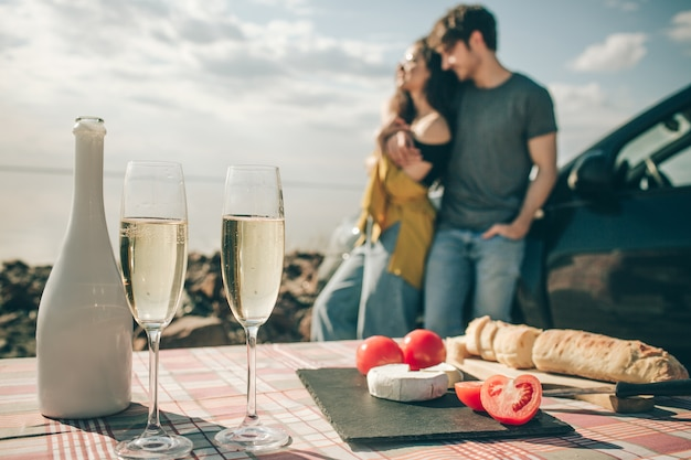 Picknick aan het water. gelukkige familie op een roadtrip in hun auto. los stokbrood, champagnekaas met witte kaas.