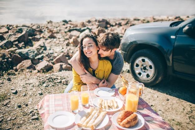 Picknick aan het water. gelukkige familie op een roadtrip in hun auto. man en vrouw reizen over zee of de oceaan of de rivier. zomerrit met de auto.