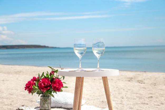 Picknick aan zee met bloemen en een glas champagne. het concept van een vakantie.