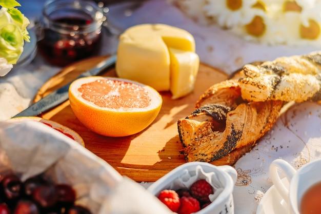 Picknick bij zonsondergang in park. fruit, kaas en croissants op tafelkleed