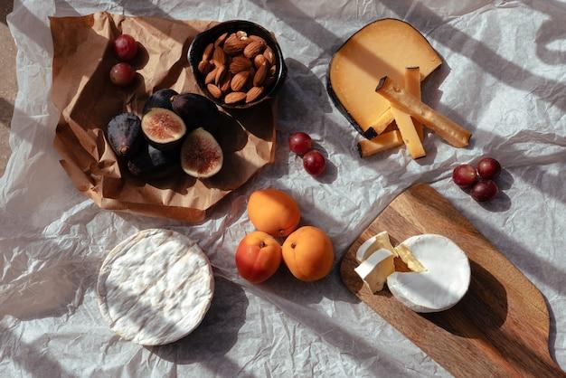Picknick bij zonsondergang met verschillende soorten kaas en fruit