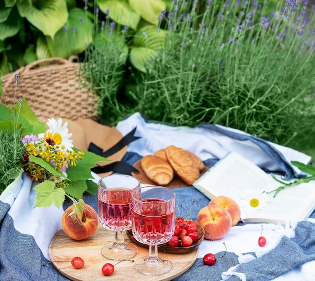Picknick buiten in lavendelvelden. rose wijn in een glas, kersen en strohoed op deken