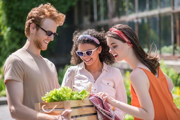 Picknick eten. roodharige glimlachende man met boodschappendoos en op zoek naar geïnteresseerde vriendinnen die op zonnige dag in het park staan